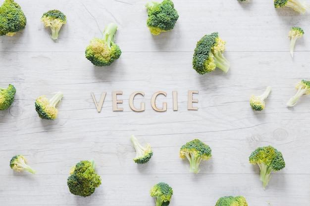 Arreglos de brócoli con letras vegetarianas en mesa de madera