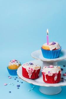 Arreglos de cupcakes de cumpleaños sobre fondo azul.