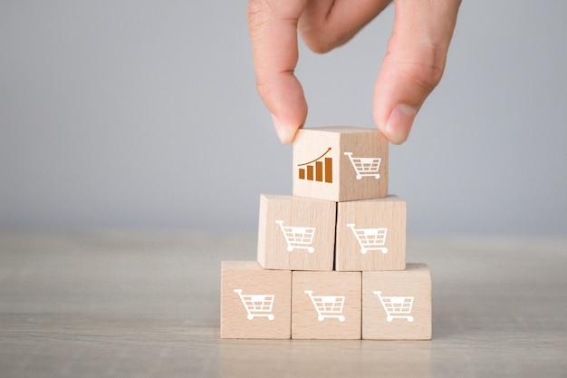 Arreglos a mano apilando bloques de madera con el icono gráfico y el símbolo del carrito de compras hacia arriba,