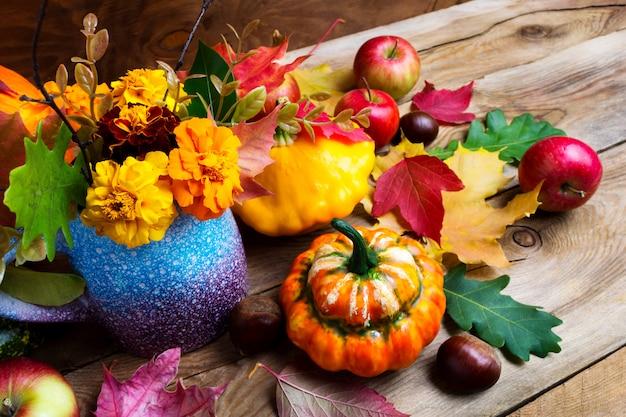 Arreglos de temporada de flores de otoño, manzanas y calabazas