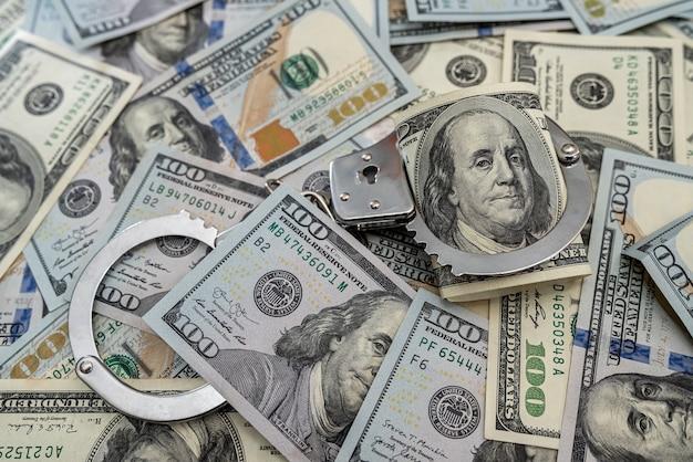 Arresto de criminales. esposas de metal en billetes de cien dólares