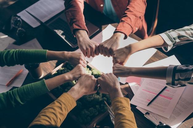 Arriba arriba vista de ángulo alto los socios de marketing recortados juntan los puños círculo redondo apoyan los objetivos de puesta en marcha