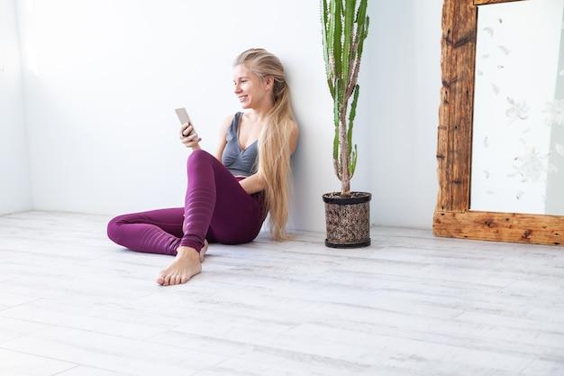 Desde arriba, la atleta femenina sentada en el piso cerca de la planta en maceta y el espejo y usando el teléfono móvil durante el descanso en el entrenamiento físico en casa