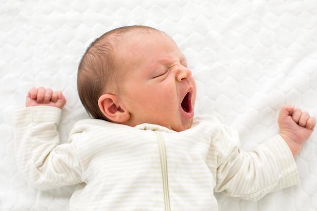 Desde arriba de un bebé recién nacido en blanco general, durmiendo y bostezando adorablemente tumbado en una manta blanca