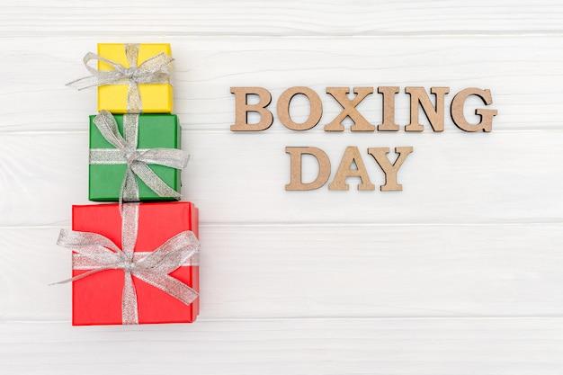 Arriba, las cajas de regalo están atadas con una cinta con las palabras boxing day en madera blanca
