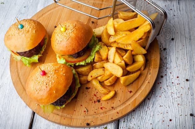 Desde arriba hamburguesa con papas fritas y una cesta de freír en el tablero de alimentos