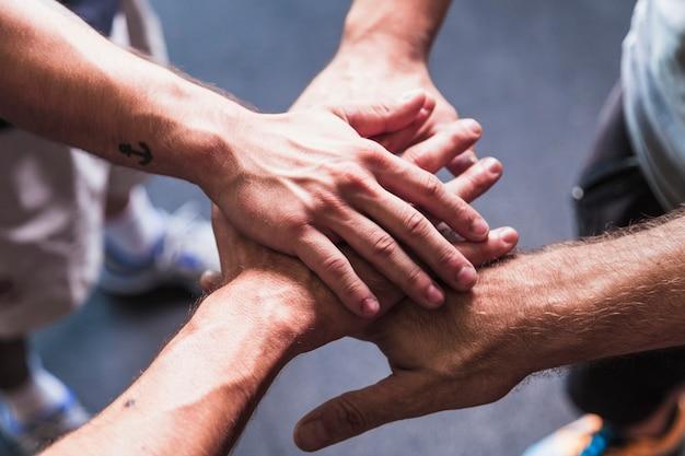 Desde arriba, hombres tomados de la mano juntos