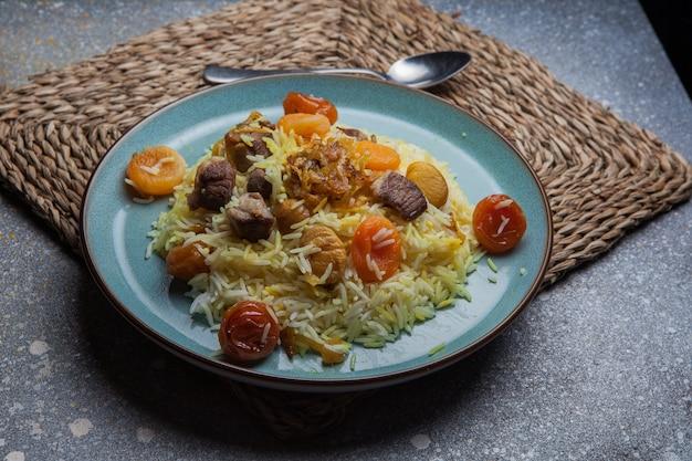 Desde arriba pilaf con frutas secas y secas y castañas y cuchara en plato redondo