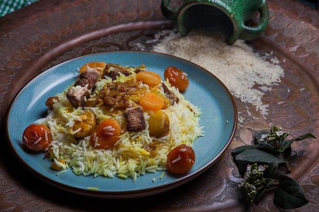 Desde arriba pilaf con frutos secos y secos y castañas y jarra en plato redondo