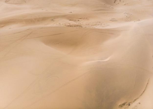 Arriba de sinuosas dunas de arena rayadas en el desierto