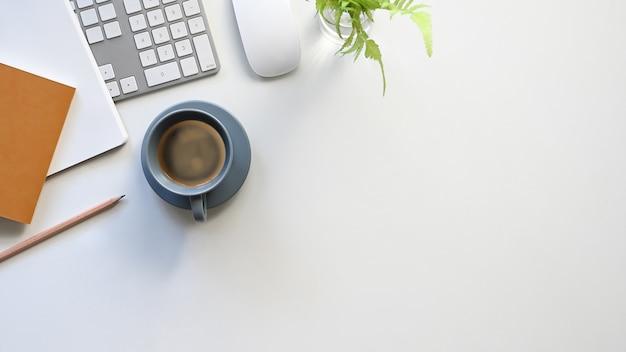 Arriba, taza de café, teclado, mouse, notas, lápiz y planta en macetas que se unen en una mesa blanca moderna. equipamiento plano de oficina. concepto de lugar de trabajo cómodo.