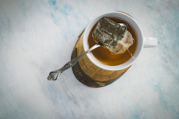 Desde arriba una taza de té caliente sobre madera con una cuchara apoyada sobre la taza que sostiene la bolsita de té