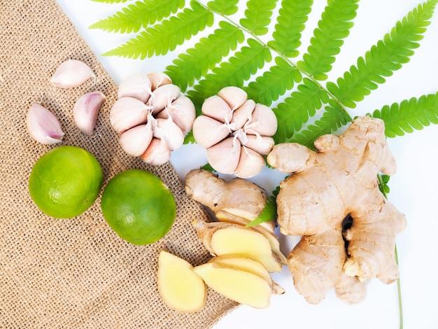 Arriba de vegetales o hierbas para uso saludable para cocinar alimentos, bebidas o medicinas con jengibre, ajo y lima limón sobre hojas de helecho.