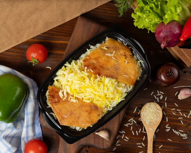 El arroz adorna, plov para llevar en envase negro en el tablero de madera.