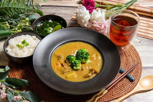 Arroz al curry de cerdo sobre fondo de madera decoración de mesa