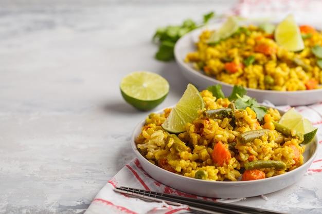 Arroz al curry vegetariano con verduras y crema de coco en platos grises. copia espacio, fondo de alimentos. concepto de comida vegana saludable, desintoxicación, dieta vegetal.