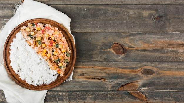 Arroz al vapor y arroz frito en un plato de madera sobre la servilleta blanca en la mesa de madera