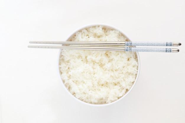 Arroz al vapor en un tazón blanco con chopstic