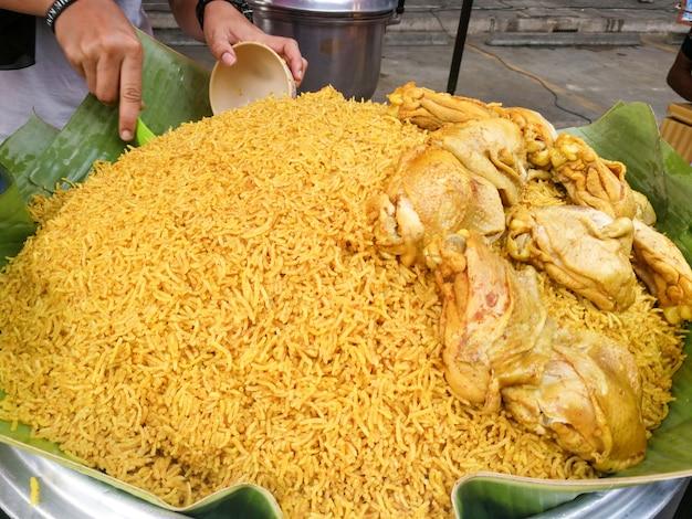 Arroz amarillo musulmán con pollo (koa mook gai) en una olla grande lista para servir con un jengibre picante