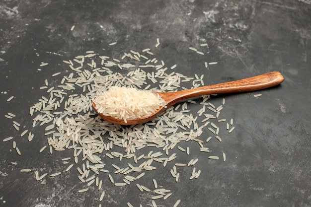 Arroz arroz en la cuchara de madera sobre la mesa oscura
