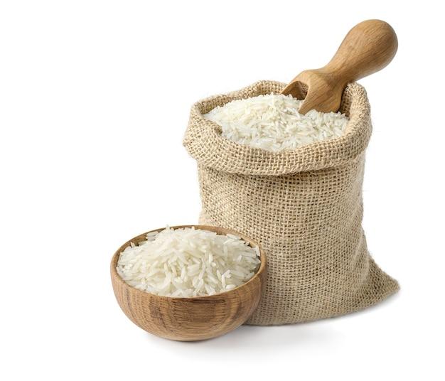 Arroz basmati largo blanco seco en cuenco de madera y saco de arpillera con pala de madera aislado sobre fondo blanco.