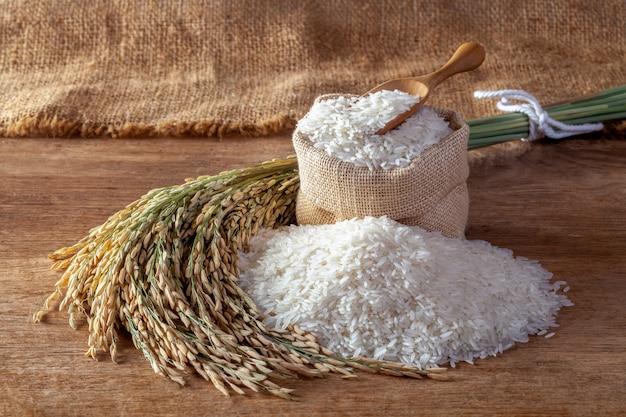 Arroz blanco (arroz jazmín) en un saco sobre un fondo de madera