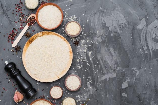 Arroz blanco crudo con especias secas; diente de ajo y molinillo de pimienta sobre fondo de hormigón