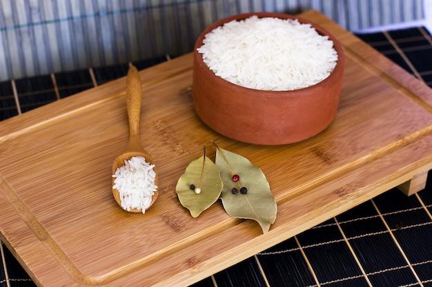 Arroz blanco en un cuenco de barro y en una cuchara de madera. hojas de laurel y
