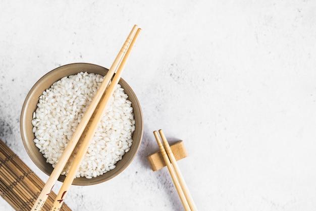 Arroz blanco en un tazón cerca de la estera de bambú