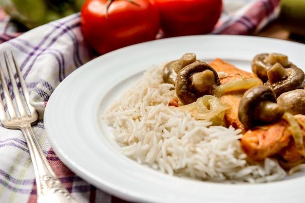 Arroz con carne y champiñones en plato blanco sobre tovel