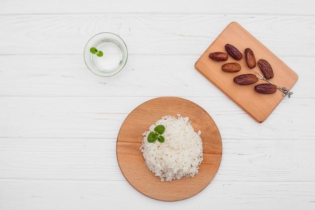 Arroz cocido con dátiles frutales en mesa de madera.