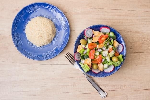 Arroz cocido con ensalada de verduras en mesa de madera.