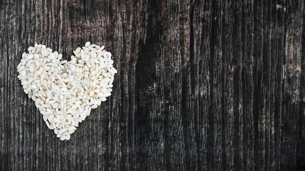 Arroz crudo hecho con el corazón en el fondo texturizado de madera negro
