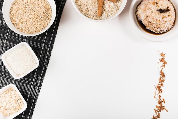 Arroz crudo sobre mantel de arroz y salsa de soja sobre fondo blanco