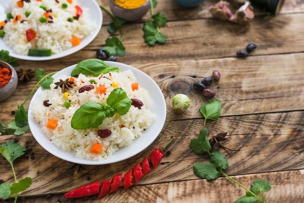 Arroz con frijoles y hojas de albahaca en un plato con ingredientes orgánicos en la mesa