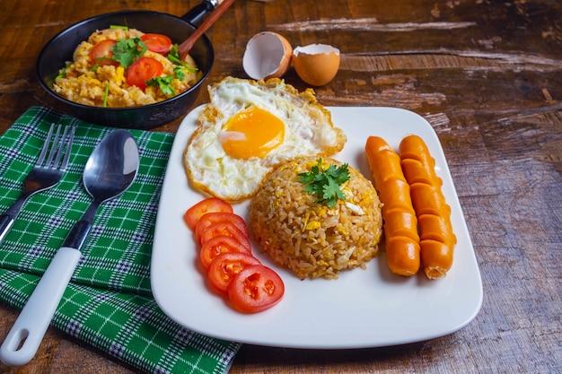 Arroz frito americano servido con huevos fritos y salchichas en la mesa