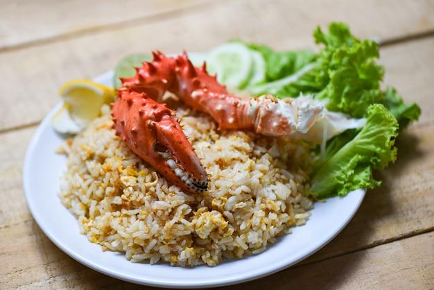 Arroz frito, cangrejo, huevo, mariscos, limón y pepino en un plato blanco, mesa de madera, garra de cangrejo