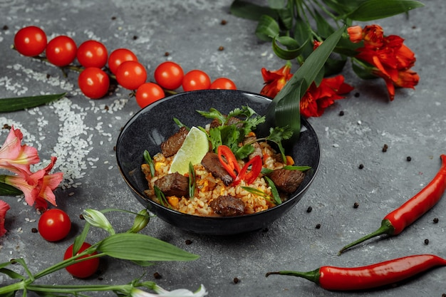 Arroz frito con carne y verduras sobre una textura gris.