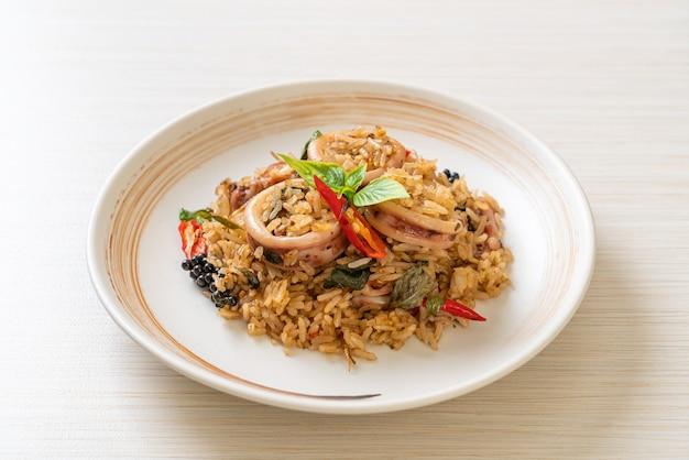 Arroz frito casero con albahaca y hierbas picantes con calamar o pulpo - estilo de comida asiática