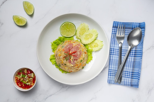 Arroz frito de cerdo fermentado servido con pepino fresco