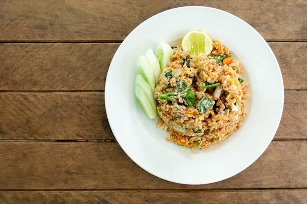 Arroz frito pollo huevo y vegetales zanahoria col rizada china cebolla verde y pepino en plato - comida tailandesa