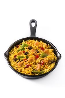 Arroz frito con pollo y verduras en sartén de hierro aislado