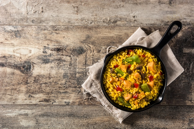 Arroz frito con pollo y verduras en sartén de hierro
