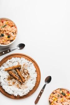 Arroz frito y de vapor chino con palitos de canela sobre fondo blanco
