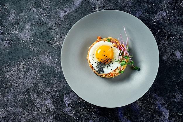 Arroz frito en wok con pollo y huevos fritos en una placa gris sobre fondo negro. comida callejera asiática. vista superior. copia espacio