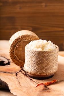 Arroz glutinoso o pegajoso de la comida asiática asiática en el mimbre de bambú en fondo de madera con el espacio de la copia
