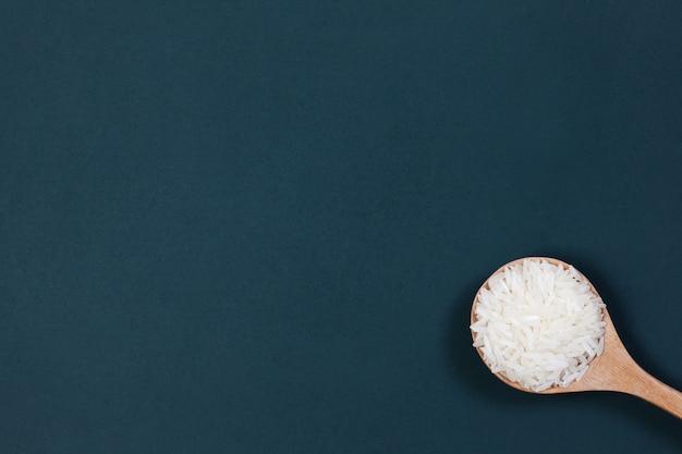 Arroz molido en la cuchara de madera sobre el fondo del tablero verde