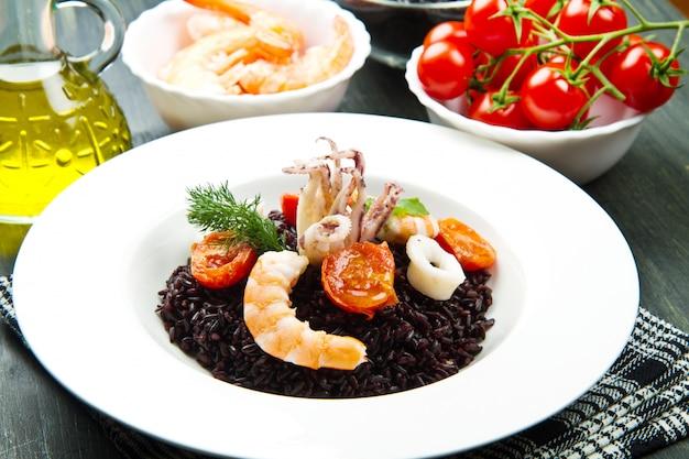 Arroz negro con rodajas de calamares, langostinos y tomate en un plato blanco