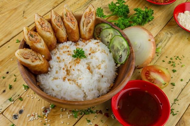 Arroz y panecillos cortados con condimentos servidos en un bol con cebolla y salsa cerca
