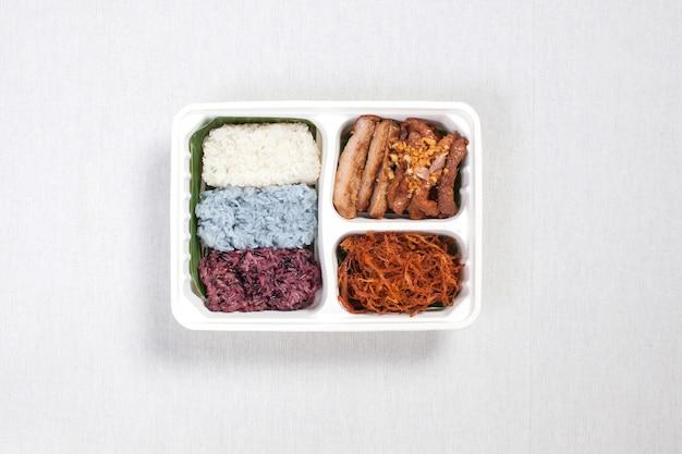Arroz pegajoso de tres colores con cerdo frito y cerdo desmenuzado puesto en una caja de plástico blanca, puesto sobre un mantel blanco, caja de comida, comida tailandesa.